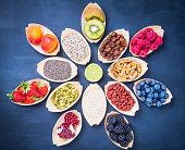 Berries, fruits, nuts, seeds top view on chalkboard.Healthy, vegan, superfood background.