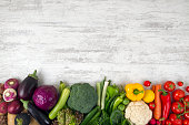 Red,green, and yellow fresh vegetables on white wood background.