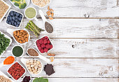 Healthy food called super foods on white, wooden background, top view with copy space