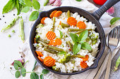 Healthy food: Fried rice with vegetables. Prepared and served in a cast-iron frying pan. Diet menu. Copy space.