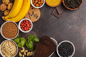 Healthy food nutrition dieting concept. Assortment of high magnesium sources. Banana chocolate spinach, buckwheat, nuts, beans, oat.