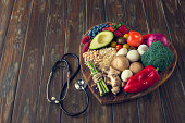 Healthy food on a heart shape cutting board. Love of food concept with fruit, vegetables, grains and high fibre foods. Rustic wood textures. There is also a stethoscope
