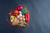 Healthy food on a heart shape cutting board. Love of food concept with fruit, vegetables, grains and high fibre foods. Rustic wood textures