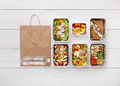Healthy food delivery, daily meals and snacks. Diet nutrition, vegetables, meat, water bottle and fruits in foil boxes and brown paper package. Top view, flat lay at white wood with copy space