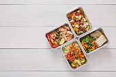 Healthy restaurant food background. Eating right concept. Fresh diet daily meals delivery. Fitness nutrition, vegetables, fish and fruits in foil boxes. Top view, flat lay on wood with copy space