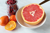 High angle view of grapefruit, kumquats and pomegranate seeds for meal.