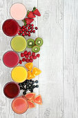 Healthy fresh fruit and juice smoothie drinks over distressed white wood background, high in antioxidants, vitamins, anthocyanins, dietary fiber and minerals.