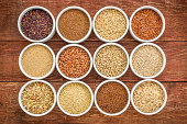 healthy, gluten free grains collection (quinoa, brown rice, millet, amaranth, teff, buckwheat, sorghum) , top view of small round bowls against rustic wood