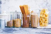 Couscous, linen seeds, noodles, quinoa, linguini pasta in glass jars over grey kitchen table.