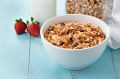 Homemade baked granola in a bowl and in a  jar, a bottle of milk and strawberries on a turquoise wooden table. Healthy breakfast