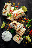 Healthy grilled chicken and parsley wraps, loaded with cheese, served with greek yogurt deep, chillies and lime slices.