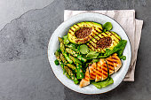 Healthy grilled chicken, grilled avocado and asparagus salad with linen seeds. Balanced lunch in bowl. Gray slate background. Top view.