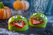 Healthy Halloween candy alternative fruit.  Apple monsters made of peanut butter, sunflower seeds and candy eye balls with spiders, spider webs, and tangerine pumpkins with celery stem on haunted hall
