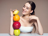 Healthy & Happy, natural organic raw fresh mix fruits concept / portrait of girl with fruits mix on the table over beige backdrop