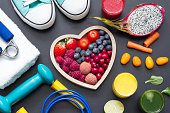 Healthy heart  diet and sport gym equipment concept on blackboard abstract