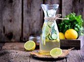 Healthy homemade lemonade made of lime, cucumber and syrup agave with ice. Rustic style, old wooden background.