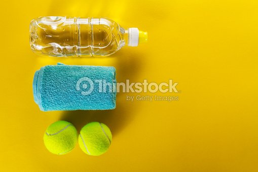 Healthy Life Sport Concept. Tennis Balls, Towel and Bottle of Water on Bright Yellow Background. Copy Space. Flat Lay.