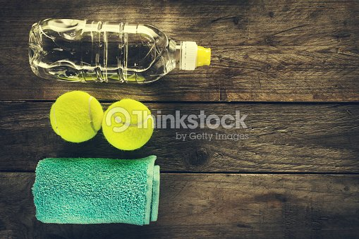 Healthy Life Sport Concept. Tennis Balls, Towel and Bottle of Water on Wooden Background. Copy Space. Top View.