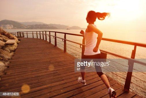 Estilo de vida saludable mujer asiática corriendo en pista de madera junto al mar : Foto de stock