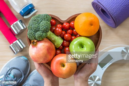 Healthy lifestyle concept, clean food good health dietary in heart dish with sporty gym aerobic body exercise workout training class equipment, weight scale and sports shoes in fitness center : Stock Photo