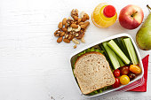 Healthy lunch box with sandwich, fresh vegetables and fruits on white wooden background. From top view