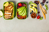 Healthy meal prep containers: Couscous with grilled chicken breast, salad, avocado, berry, apple, nuts and dry dates. Keto, ketogenic diet, low carb, healthy food concept. Top view