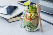 Healthy lunch in glass jar in workspace