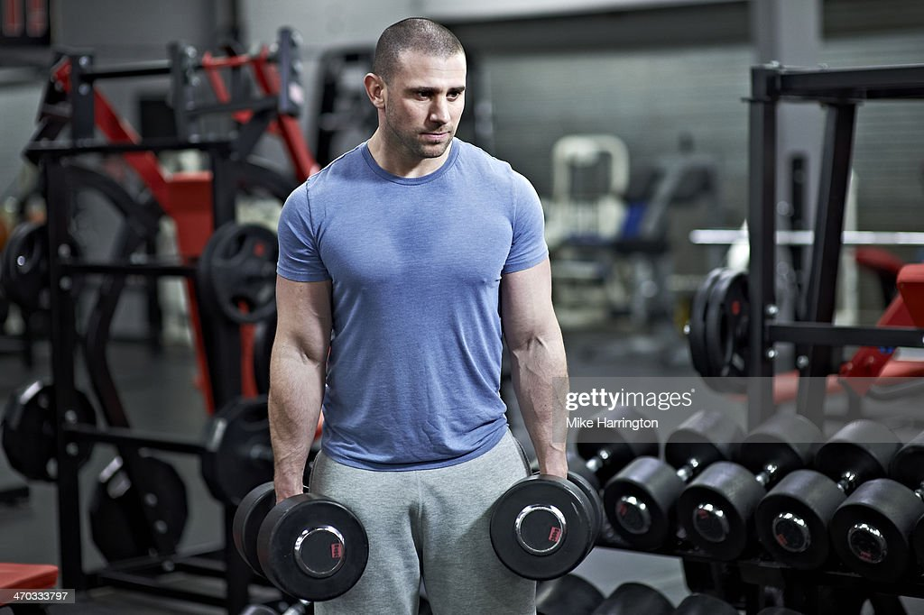 Healthy Male Holding Dumbbells in Gym