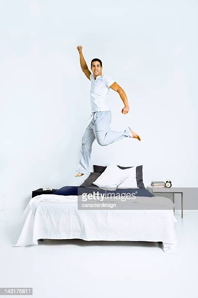 Healthy man jumping on bed