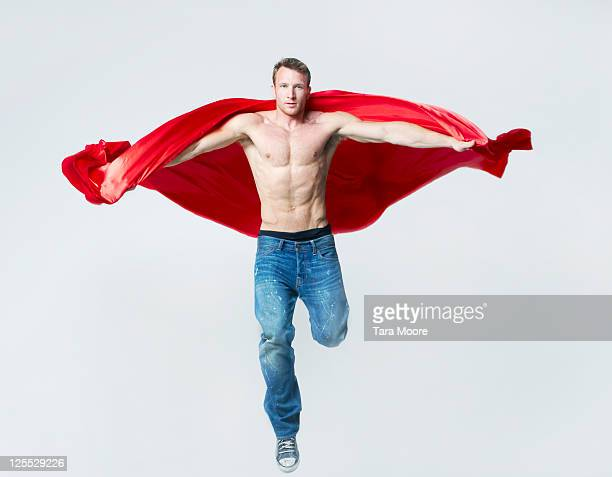 healthy man jumping with red cape
