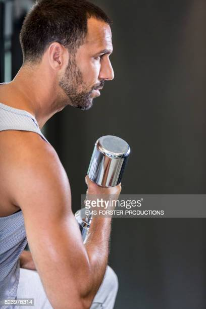 healthy man with three day beard wearing axillary shirt doing biceps curls with silver colored dumbbell in gym on a bench