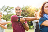 """Mature man stretching at park while listening to music with group of people. Senior multiethnic man working out with his freinds. Healthy man with class doing stretching exercises.""""r"""
