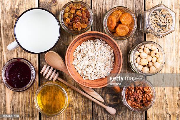 Healthy morning muesli ingredients on rustic wooden board, top view