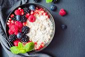 Healthy organic breakfast porridge topped with raspberries, blueberries and mint leaves