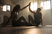 Healthy man and woman sitting on floor and giving each other high five at the gym. Fitness people after successful exercising session in cross training gym.
