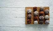 Healthy raw energy balls with cocoa, coconut, sesame, chia on a white textured wooden background.  Vegan chocolate truffles. Copy space