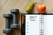 Dumbbells with fruits and open notebook on wooden desk. Healthy resolutions for the New Year 2017.