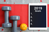 Dumbbells with mandarin and tablet computer. Healthy resolutions for the New Year 2019.