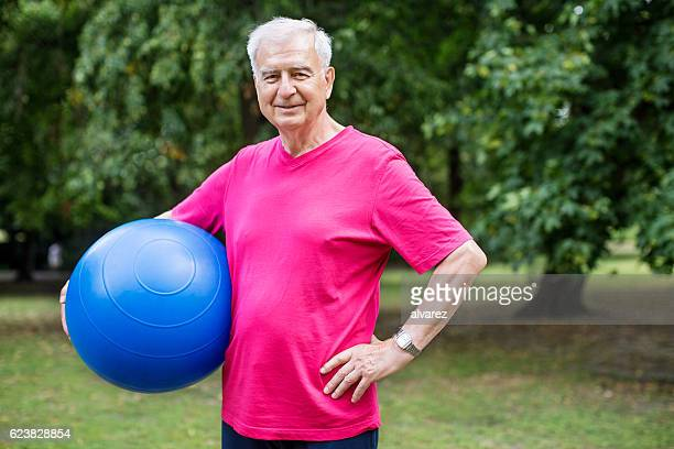 Healthy senior man at park with pilates ball