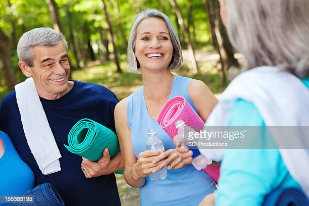 Healthy seniors laughing together during outdoor group fitness class