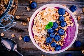 healthy smoothie bowl with granola, banana and fresh blueberries on wooden background