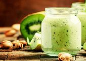 Healthy Smoothies from kiwi and pistachios, vintage wooden background, selective focus