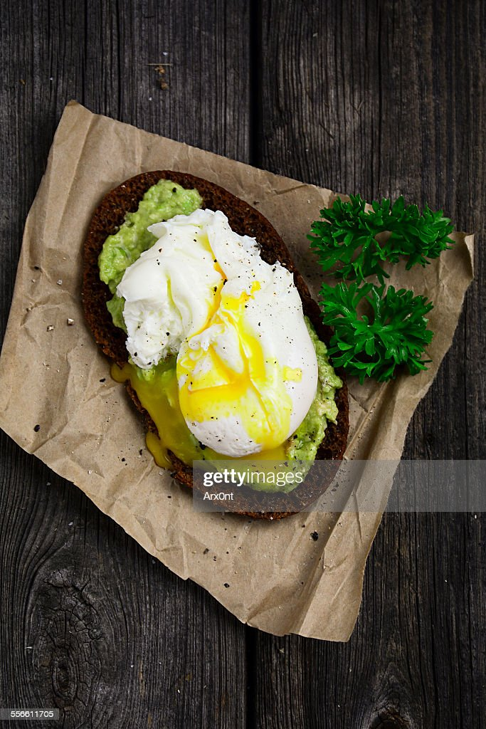 rye toast with mashed avocado and poached egg on parchment paper garnished with cracked black pepper and curly parsley. Rustic wooden table background, top view