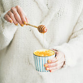 Healthy vegan turmeric latte or golden milk with honey in female hands, square crop