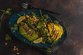 Healthy vegan avocado, chickpeas, kale salad in a vintage blue plate on a dark rusty background. Vegan food concept.