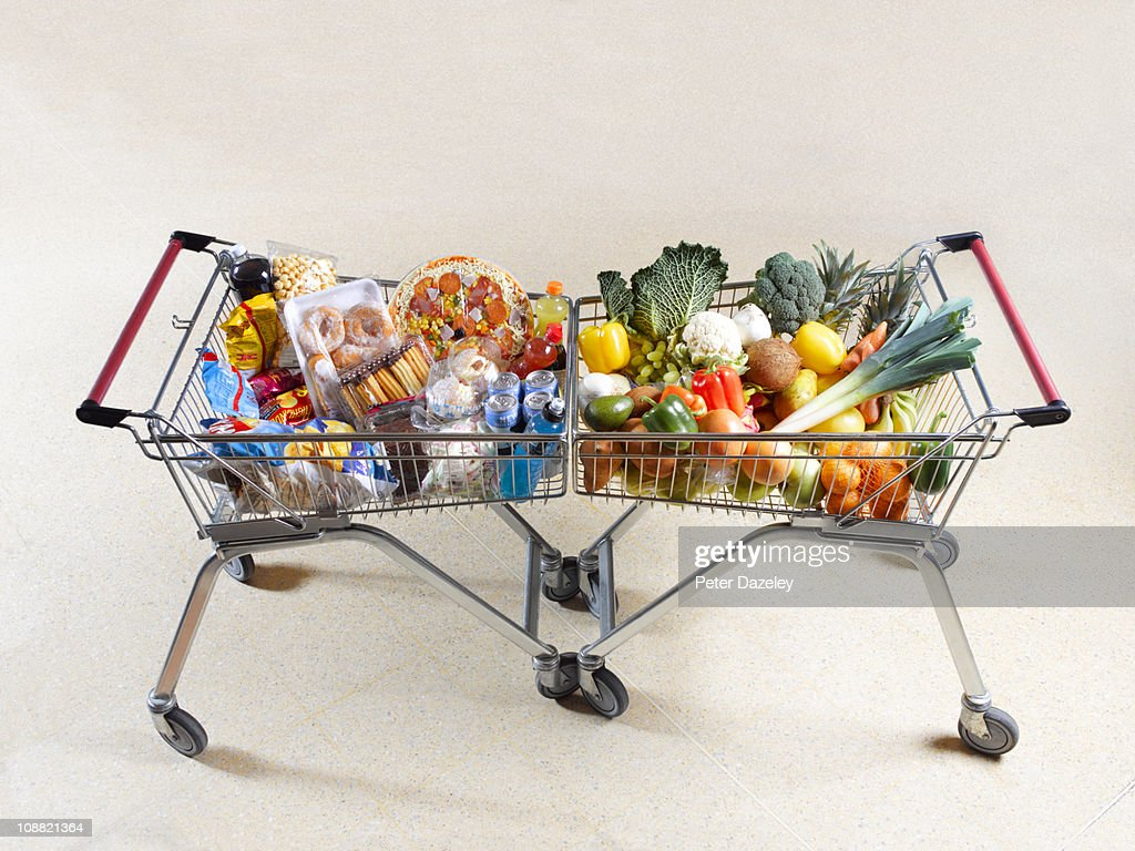 Healthy vs unhealthy shopping trolleys : Stock Photo