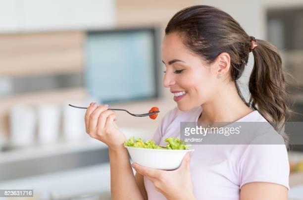 Gesunde Frau zu Hause essen einen Salat