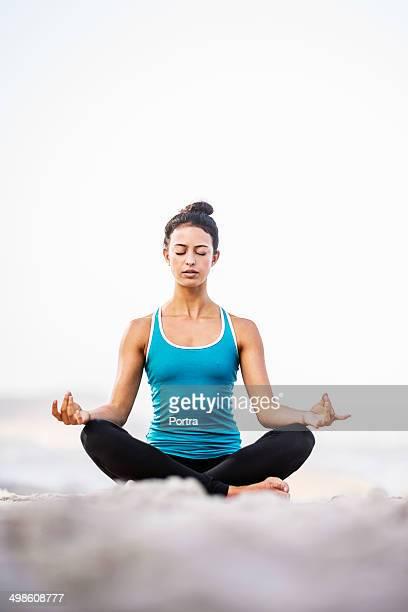 Healthy woman doing meditation on the beach.