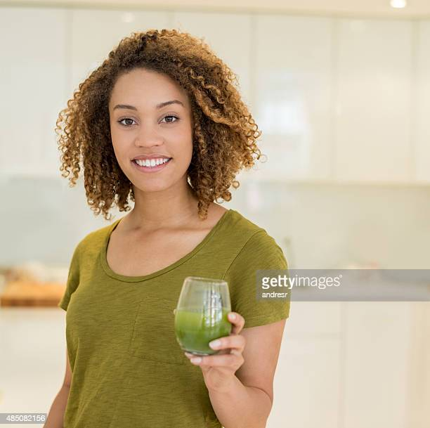 Healthy woman drinking a green smoothie