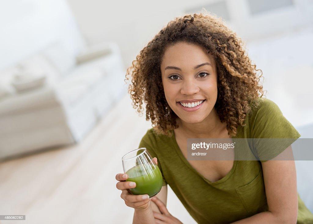Healthy woman drinking an organic green juice : Stock-Foto